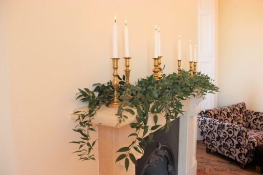 Brass candlesticks, white and foliage mantelpiece decor, styling by Elizabeth Weddings
